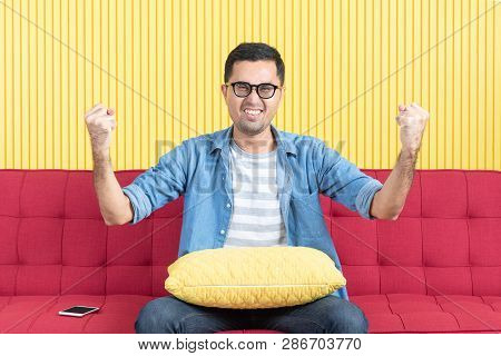 Shot Of Young Asian Handsome Bearded Man, Wearing Eyeglasses In Denim Shirt, Sitting On Red Sofa, Ta