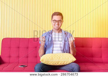 Shot Of Young Asian Handsome Bearded Man, Wearing Eyeglasses In Denim Shirt, Sitting On Red Sofa, Bo