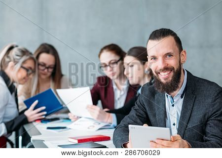 Idle Employee. Team Member Slacking Off During Business Meeting. Smiling Carefree Man With Tablet At