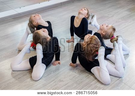 Little Girls Do Gymnastics In A Dance Class. The Concept Of Sport, Education, Childhood, Hobbies And