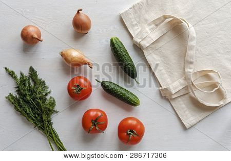 Fabric Re-usable Shopping Bag With Groceries Scattered Around Including Tomatoes, Onions, Cucumber A