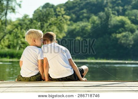 Little Boy Whispers To The Other Ear, Sitting On The Bank Of The River