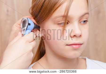 Female pediatrician examines elementary age girl's ear in pediatric clinic. Doctor using a otoscope or auriscope to check ear canal and eardrum membrane. Child ENT check concept