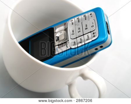A Mobile Phone In White Cup