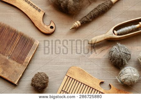 Several Ancient Traditional Female Craft Tools On Brown Wooden Background