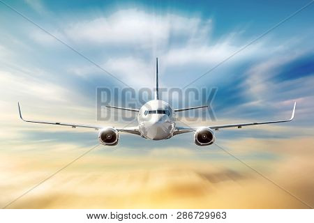 Airplane With Motion Blur Effect Is Flying In Orange Clouds At Sunset. Concept Aviation Air Transpor