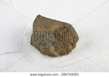 Mineral Chalcopyrite, Copper Pyrite From Grekhovskoe, Altai, Russia On White Cement Background. Copp