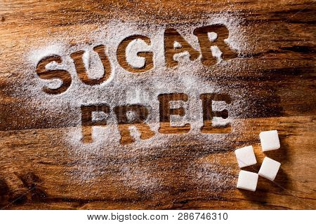 high angle view of a wooden table sprinkled with sugar where you can read the text sugar free and some sugar cubes