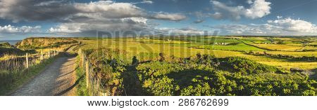 Irish countryside panorama of the green fields and road under the rainy cloudy sky. Northern Ireland landscape. Picturesque grass covered meadows below the colorful sky. Ideal image for the collages.