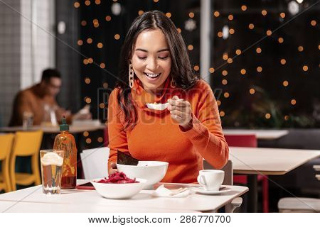 Pleasant long-haired woman tasting soup with pleasure. poster
