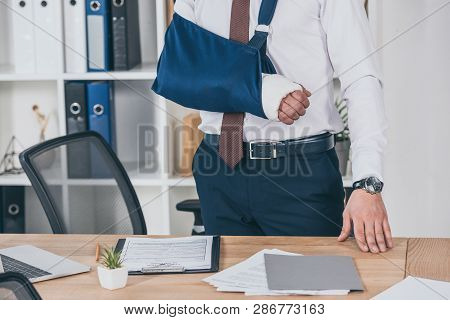 Cropped View Of Worker With Broken Arm In Bandage Standing Near Table In Office, Compensation Concep