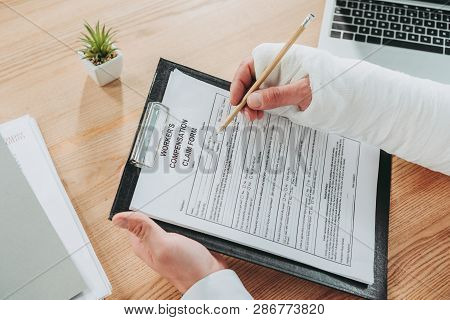 Cropped View Of Worker With Broken Arm In Gypsum Sitting At Table And Writing On Compensation Form I