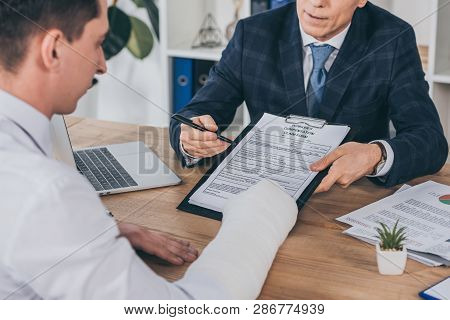 Businessman In Blue Jacket Giving Form For Compensation Claim To Worker With Broken Arm At Table In