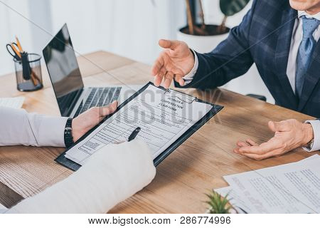 Cropped View Of Worker With Broken Arm Signing Form For Compensation Claim  Opposite To Businessman