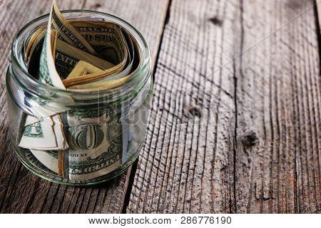 Dollar Bills In Glass Jar On Wooden Background. Saving Money Concept