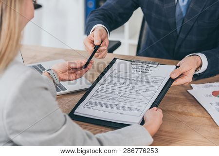 Cropped View Of Businessman Giving Woman Pen And Form For Compensation Claim Over Table With Laptop