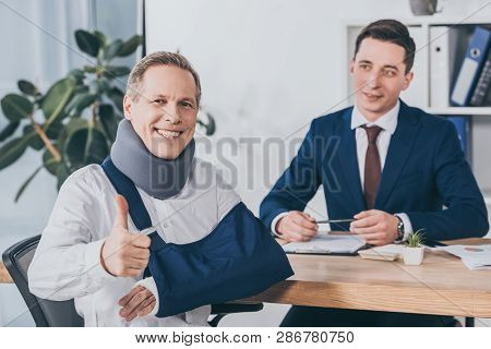 Businessman Sitting At Table Wile Worker In Neck Brace And Arm Bandage Showing Thumb Up In Office, C