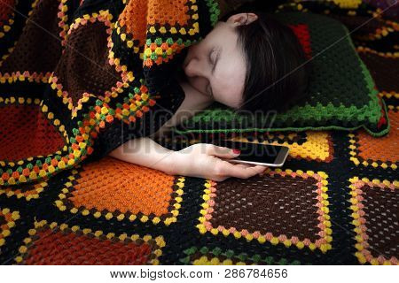 Attachment To New Technologies. A Woman Is Sleeping While Holding A Phone In Her Hand.
