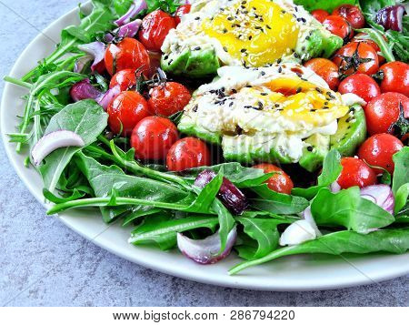 Avocado With Egg, Arugula And Cherry Tomatoes On A Plate. Plate With A Healthy Meal. A Healthy Healt