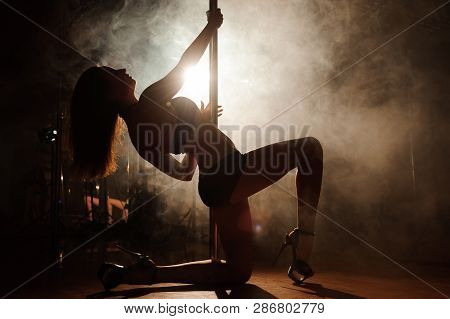 Pole Dancing, Attractive Sexy Woman Pole Dancer Performing In A Smoke.