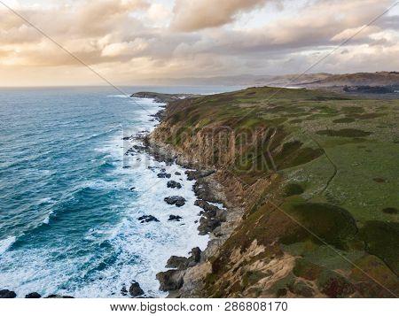 Aerial view of waves crashing along the rocky California coast near San Francisco.
