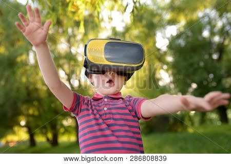Little Boy Using Virtual Reality Headset Outdoor. Vr, Vr Glasses, Augmented Reality Experience. Kids