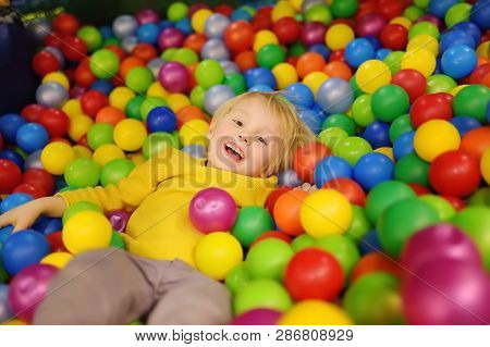 Happy Little Boy Having Fun In Ball Pit With Colorful Balls. Child Playing On Indoor Playground. Kid