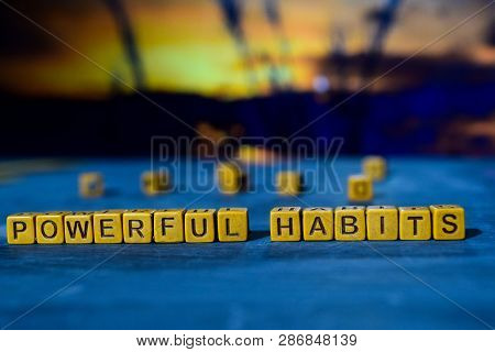Powerful habits on wooden blocks. Cross processed image with bokeh background poster