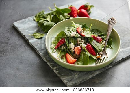 Salad with spinach, feta and strawberries, sprinkled with pumpkin and sunflower seeds