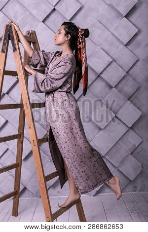 Prepossessing Poser Wearing Dress Standing On Ladder During Studio Shooting