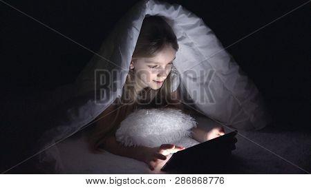 Child Playing Tablet In Dark Night, Girl Browsing Internet In Bed, Not Sleeping