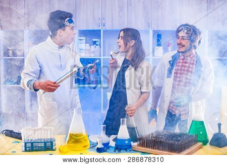 Cheerful Funny Scientists Standing In Smoke In The Laboratory.