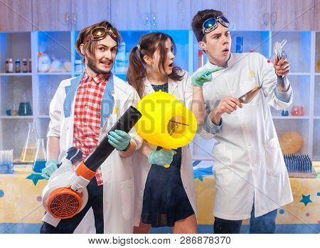 Group Of Playful Teens Posing At Camera Having Experiments In Class Of Chemistry And Physics.