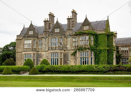 Muckross House And Gardens Against Cloudy Sky. It Is A Mansion Designed In Tudor Style, Located In T