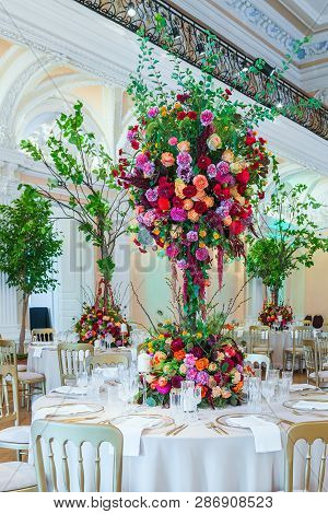 Wedding Table Decoration. Beautiful Bouquet Of Flowers On The Table, Next To Plates, Crystal Glasses