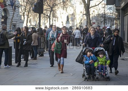London - February 15, 2019: Mom Pushes A Stroller With Twins Down The Street In A Crowd On The Stran