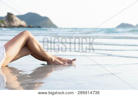 Beautiful Woman's Legs Relaxing On The Beach With Light Of Sunset, Holiday Concept