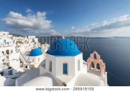 Spectacular View On White And Blue Houses In Oia Village On Santorini Island In Greece