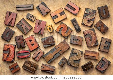 random letters overhead background - vintage letterpress wood type of different fonts  (inverted image)  against brown handmade bark paper