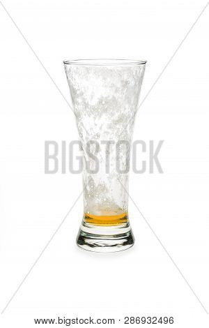Almost Empty Pilsner Beer Glass Isolated Against White Background.
