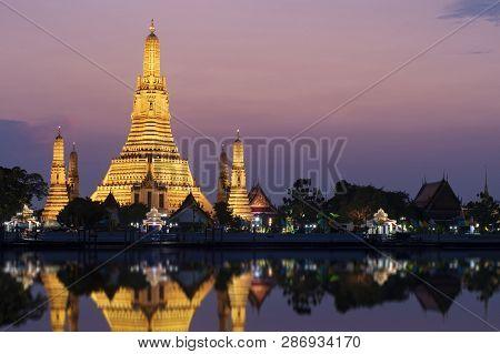 Wat Arun Landmark Of Bangkok, Thailand At Dusk With Water Reflection At Choa Phraya River Twilight.