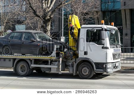 Varna, Bulgaria, February 28, 2019. A Tow Truck With Hook And Chain Transports A Car Without A Front