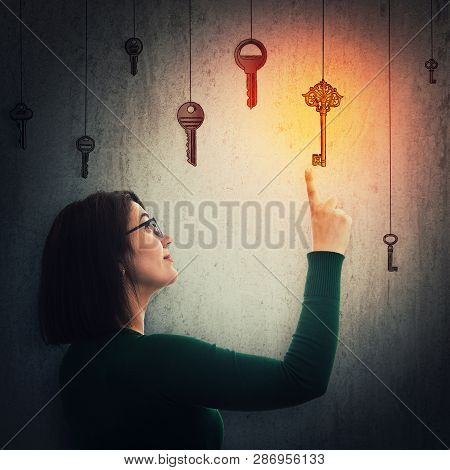 Young Woman Wearing Glasses Pointing Index Finger Up Showing To The Magic Golden Key. Concept Of Bus