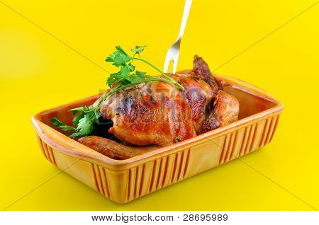 Chicken Baked in their own juice in a ceramic bowl with a sprig of parsley poster
