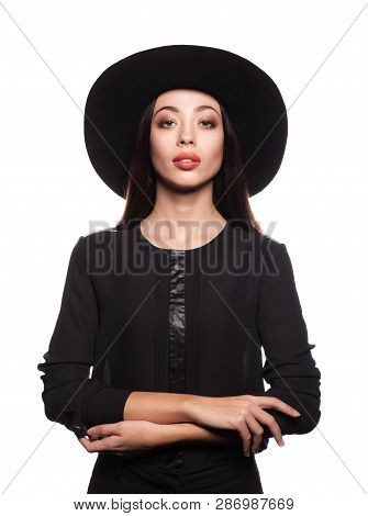 Elegant Brunette Woman In Elegant Black Dress And Black Hat. Beautiful Woman With Red Lips And Cross