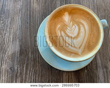 A Ceramic Cup Of Latte Art Sitting On A Wooden Table.