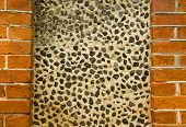 Wall decorated with small pebble stones. Architecture background details. poster