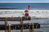 Fun bum with sign waves flag along beach in Ocean Grove, NJ, on a sunny winter day poster
