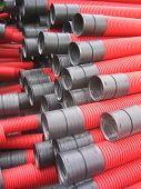 Red curvilinear pvc tubes stack at construction site poster