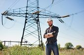 Engineer with white hard hat under the power lines. Engineer work at an electrical substation. poster